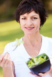 Middle aged woman salad. Healthy middle aged woman eating bowl of salad Royalty Free Stock Images