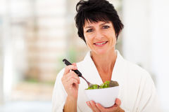 Middle aged woman salad. Beautiful middle aged woman with healthy salad at home Stock Images