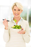 Middle aged woman salad. Happy middle aged woman eating green salad Royalty Free Stock Photos