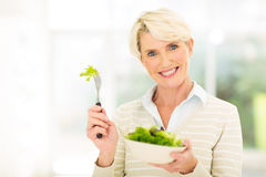 Middle aged woman salad. Pretty middle aged woman eating vegetable salad Stock Images