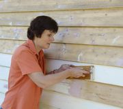 Middle-aged Woman Sanding Paint From Weatherboards. Stock Photos