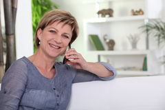 Middle-aged woman sat on couch Royalty Free Stock Photo