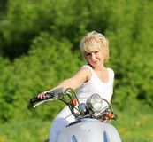 Middle aged woman on scooter Stock Images