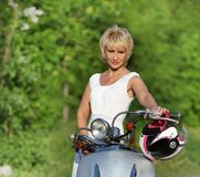 Middle aged woman on scooter Royalty Free Stock Image
