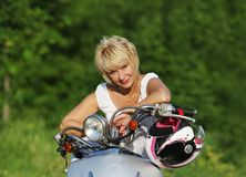 Middle aged woman on scooter Royalty Free Stock Photo