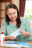 Middle Aged Woman Scrapbooking At Home Royalty Free Stock Photo