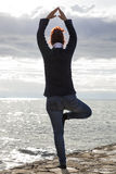 Middle aged woman at the seaside performing Yoga Royalty Free Stock Photos