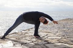 Middle aged woman at the seaside performing Yoga Stock Image
