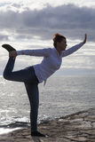 Middle aged woman at the seaside performing Yoga Stock Photo