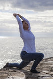 Middle aged woman at the seaside performing Yoga Royalty Free Stock Photo