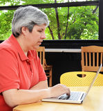 Middle-aged woman seated browsing on laptop Stock Photo