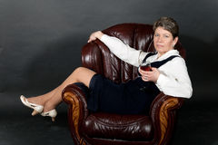 Middle aged woman, seated in a leather chair Royalty Free Stock Photography