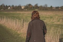 Middle-aged woman seen walking in a nature reserve using a walking pole. Middle-aged woman seen walking away from the camera, using a Walking Pole while walking stock photos