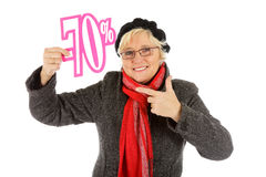 Middle aged woman, seventy percent discount sign. Attractive middle aged caucasian woman pointing at seventy percent discount sign. Studio shot. White background Royalty Free Stock Image