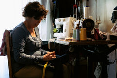 Middle aged woman sewing Stock Images