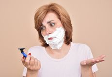 Woman with shaving foam on her face holding and looking sadly at a razor stock photos