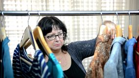Middle-aged woman shopper discovers that a blouse on clothes rack is dirty. Obviously, the middle aged woman does not like a second-hand shop. That is probably stock video footage