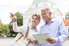 Middle-aged woman showing something to man holding map outdoors Royalty Free Stock Images