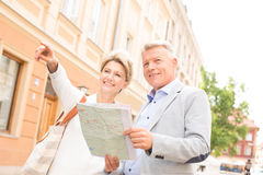 Middle-aged woman showing something to man with road map in city Royalty Free Stock Photo