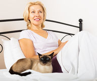 Middle-aged woman with siamese cat Royalty Free Stock Image