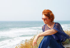 Middle-aged woman sits by the sea Stock Image