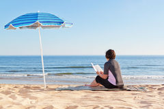 Middle-aged woman sitting on the beach reading a book. Stock Photo