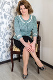 Middle-aged woman sitting on chair in  living room Stock Photos