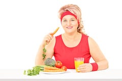 Middle aged woman sitting and eating vegetables and drinking jui Royalty Free Stock Images