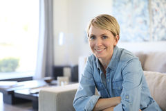 Middle-aged woman sitting at home on sofa Stock Images