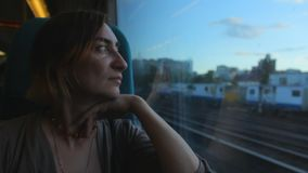 Middle aged woman sitting near the window in the train, looking and thinking about the future. Evening stock video