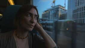 Middle aged woman sitting near the window in the train, looking and thinking about her life. Evening stock video