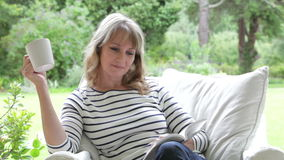 Middle Aged Woman Sitting Outdoors Reading Book stock video footage