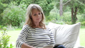 Middle Aged Woman Sitting Outdoors Reading Book stock footage