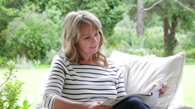 Middle Aged Woman Sitting Outdoors Reading Magazine stock video
