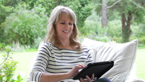 Middle Aged Woman Sitting Outdoors Using Digital Tablet stock video
