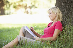 Middle Aged Woman Sketching In Countryside Leaning Against Tree Royalty Free Stock Image