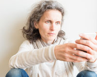 Middle aged woman with smart phone Royalty Free Stock Images