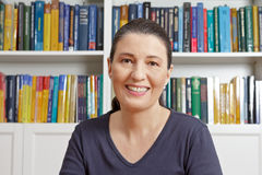 Middle aged woman smile books. Happy middle aged woman with blue t-shirt in front of lots of books, having an live video chat with her family or onlne dating Stock Photography