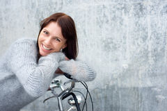 Middle aged woman smiling and leaning on bicycle Royalty Free Stock Image