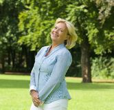 Middle aged woman smiling outdoors Stock Photo