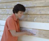 Middle-aged Woman Smoothing Putty on Weatherboards. Royalty Free Stock Photography