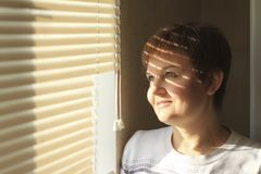 Middle-aged woman standing in front of a window in daylight, dreaming and smiling, a shade of blinds on her face. Close-up portrait Royalty Free Stock Photography