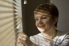 Middle-aged woman standing in front of a window in daylight, dreaming and smiling, a shade of blinds on her face. Close-up portrait Royalty Free Stock Images