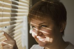 Middle-aged woman standing in front of a window in daylight, a shade of blinds on her face. Close-up portrait Royalty Free Stock Image