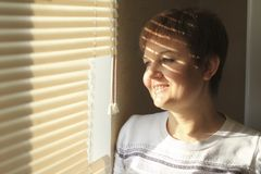 Middle-aged woman standing in front of a window in daylight, a shade of blinds on her face. Close-up portrait Stock Photos