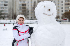 Middle-aged woman standing near a snowman in  city Royalty Free Stock Photo