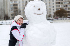 Middle-aged woman standing near a snowman in  city Stock Photos
