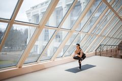Middle aged woman standing in One legged chair exercise, Eka Pada Utkatasana pose, working out, wearing sportswear, full length in. Front of large windows Stock Images