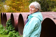 Middle aged woman standing outdoor in autumn near big old meal construction pipes royalty free stock images