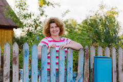Middle-aged woman stands at the gates country Stock Photo